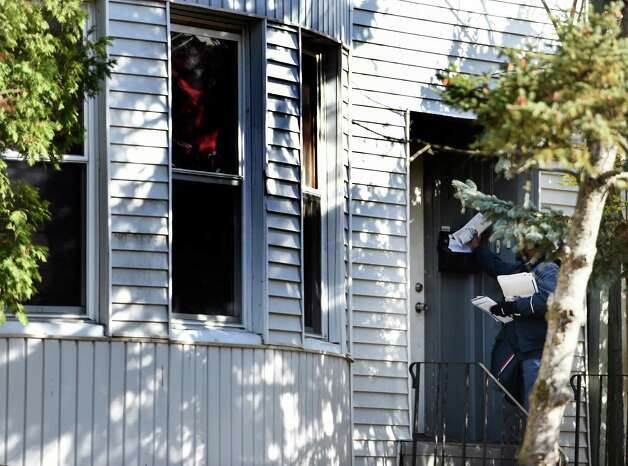 A Postal Service letter carrier drops mail at 461 Hamilton Street, the scene of an alleged underage drinking party, Tuesday afternoon, Nov. 18, 2014 in Albany, N.Y.  Police responded to a call early Sunday morning and found five intoxicated 19-year-old men, all University at Albany students. One of them, Trevor Duffy, 19, of Bronx, died at Albany Medical Center after excessive alcohol consumption.  (Skip Dickstein/Times Union) Photo: SKIP DICKSTEIN / 00029538A