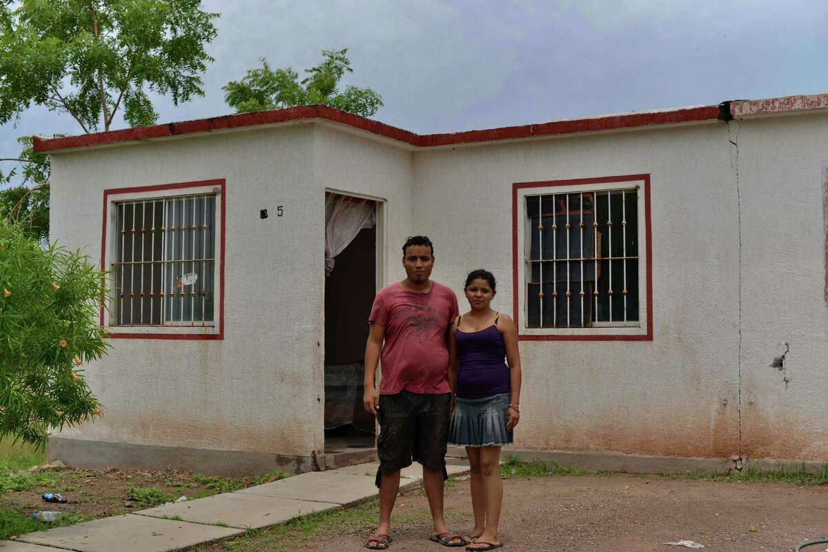In this July 21, 2015 photo, Mauro Diaz and his wife, Itza Veronica Retana, pose outside of an abandoned house where they have taken refuge in Guamuchil, Mexico. Like Diaz and his wife, dozens of families left the village of Ocurahui after drug gangs, particularly the Sinaloa cartel, pressured local farmers to plant opium poppies in order to counter falling prices for marijuana. Residents who didn't want to grow drug crops faced kidnappings or even death. Despite his humble roots, Joaquin