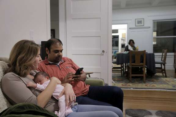Husband and wife, Ish Harshawat and Emma Acker, with their 3-week-old daughter Maya, in their San Francisco, Calif., home on Tuesday, October 20, 2015. The couple is mired in a housing battle with a tenant who refuses to leave despite the couple's family hoping to move into the apartment.