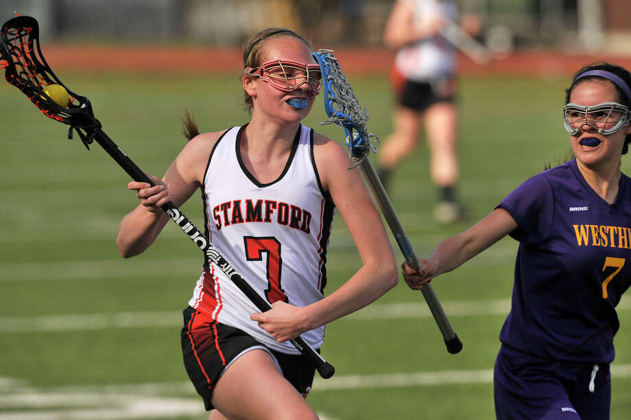 Stamford's Jennifer Krupa meets resistance from Westhill's Kelly Finn during their lacrosse game at Stamford High School in Stamford, Conn., on Thursday, April 30, 2015. Stamford won, 14-0. Photo: Jason Rearick / Jason Rearick / Stamford Advocate