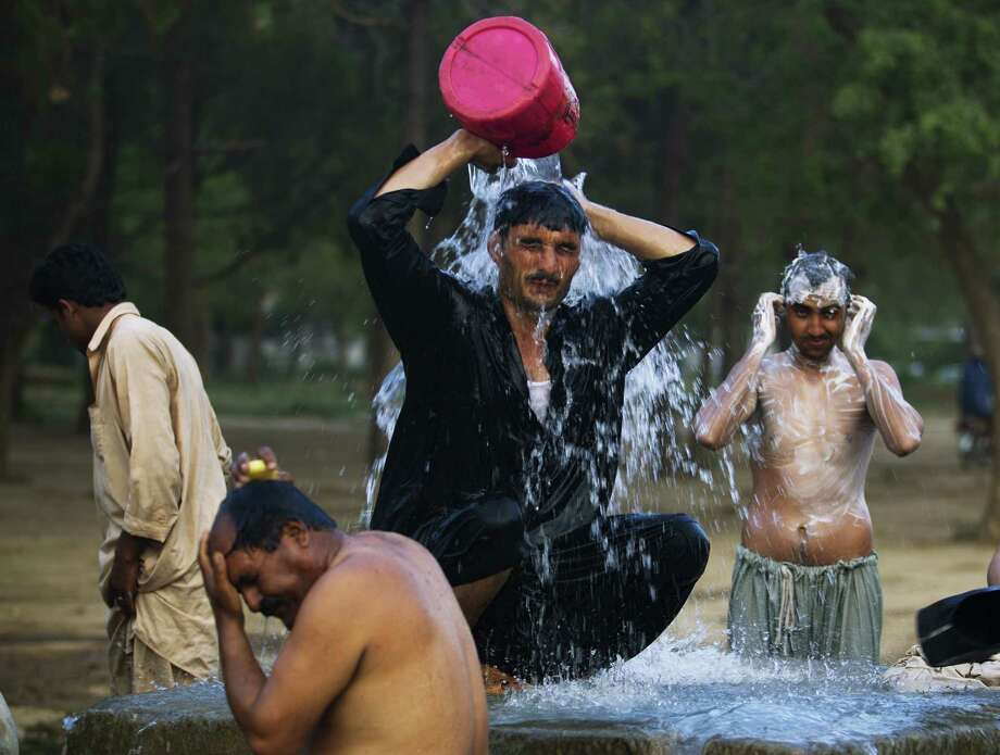 FILE - In this June 3, 2013 file photo, Pakistani laborers bathe at a leaked water hydrant at the end of a day on the outskirts of Islamabad. With each degree, unrestrained global warming will singe the overall economies of three quarters of the nations in the world and widen the north-south gap between rich and poor countries, a new economic and science study found. Compared to what it would be without more global warming, the average income globally will shrivel 23 percent at the end of the century if heat-trapping carbon dioxide pollution continues to grow at current trajectories, according to a study published Wednesday in the scientific journal Nature. (AP Photo/B.K. Bangash, File) Photo: B.K. Bangash, STF / AP