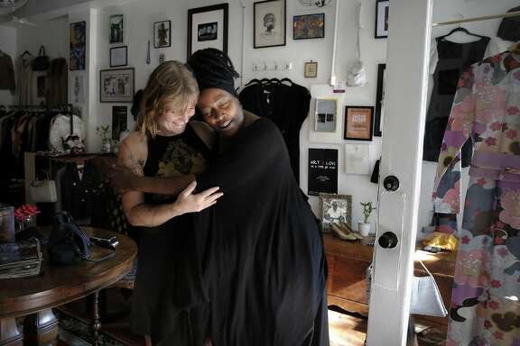 Trinity Cross, (left) owner of the field day & friend handcrafted boutique which is nearby gets a hug from Regina Evans during a visit to see her friend. Regina's Door is a consignment shop started by Regina Evans, a survivor of sex trafficking, who is celebrating her one year anniversary in Oakland, Calif., at the shop she uses to raise money and awareness for survivors of human trafficking and employs women who survived the sex trade. Regina is seen in her shop on Fri. October 16, 2015.