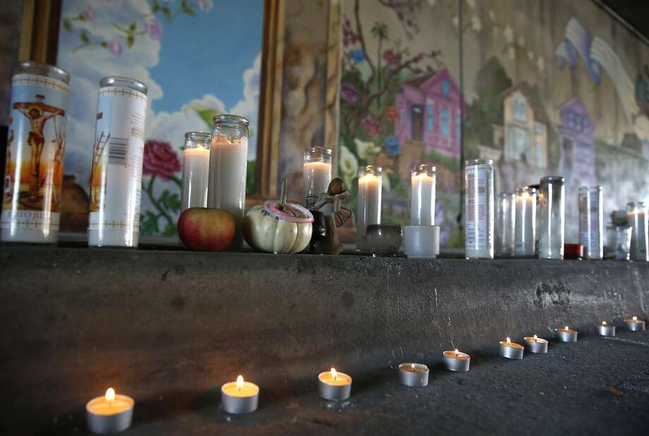 Candles line the curb at a dedication ceremony for the Superheroes Mural Project on West Street in Oakland, Calif. on Wednesday, Oct. 21, 2015. Artist Antonio Ramos was shot and killed while working on the mural on Sept. 29. Photo: Paul Chinn, The Chronicle