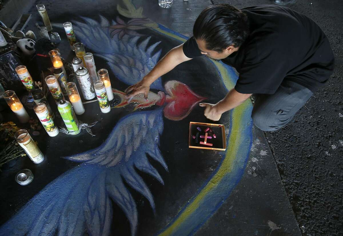 Daniel Panko sketches a design in chalk before a dedication ceremony for the Superheroes Mural Project on West Street in Oakland, Calif. on Wednesday, Oct. 21, 2015. Artist Antonio Ramos was shot and killed while working on the mural on Sept. 29.