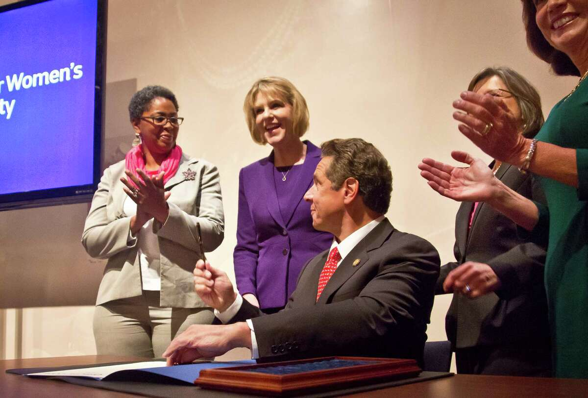 Gov. Andrew Cuomo, center, hands his signing pen to school safety agent Kangela Moore, far left, after he signed a series of bills that aims to ensure equality for women in the workplace and provide stronger laws for victims of domestic violence, Wednesday, Oct. 21, 2015, in New York. Moore, an activist for women's equality, introduced Gov. Cuomo at the signing ceremony at Hunter College's Roosevelt House. (AP Photo/Bebeto Matthews) ORG XMIT: NYBM103