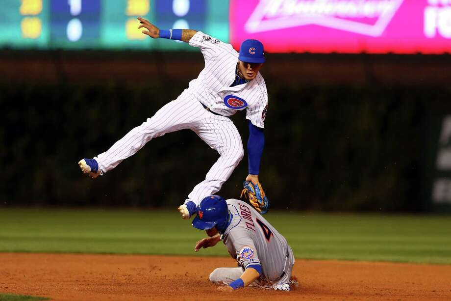 CHICAGO, IL - OCTOBER 21:  Wilmer Flores #4 of the New York Mets steals second in the first inning against Javier Baez #9 of the Chicago Cubs during game four of the 2015 MLB National League Championship Series at Wrigley Field on October 21, 2015 in Chicago, Illinois.  (Photo by Elsa/Getty Images) Photo: Elsa, Staff / 2015 Getty Images