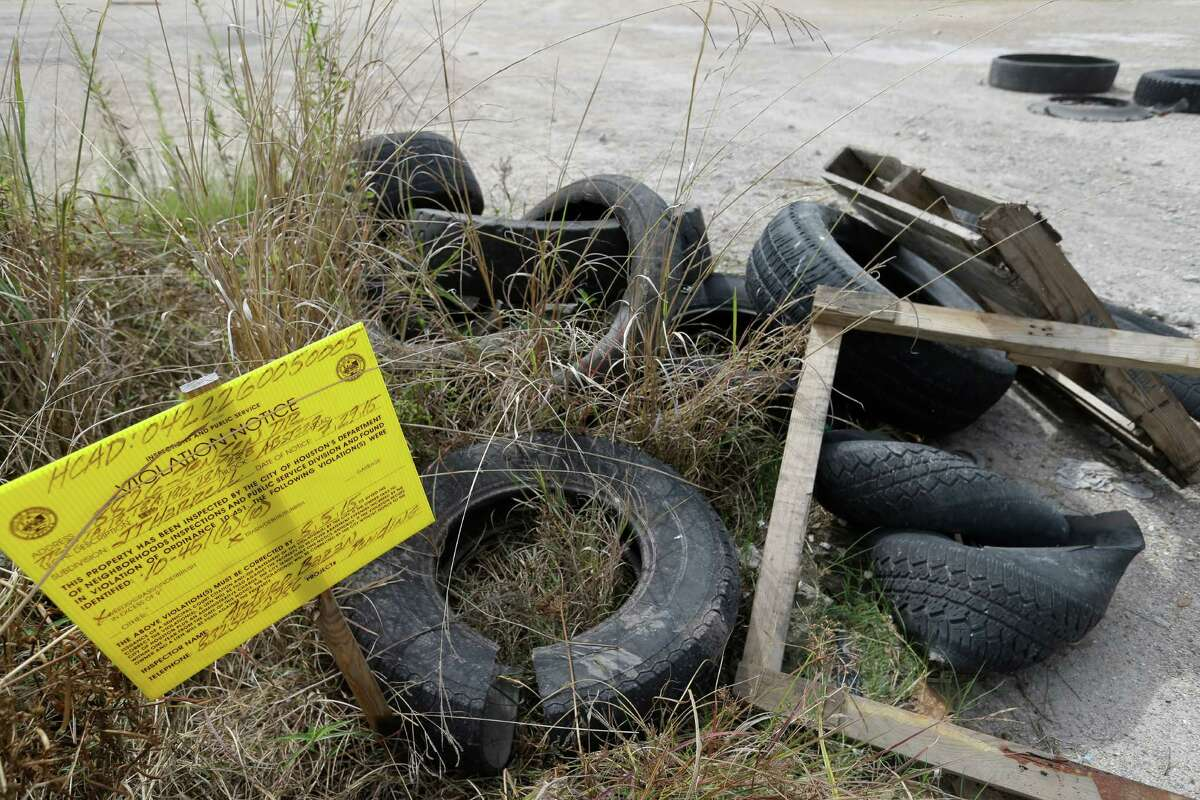 A City of Houston violation notice is posted among tires and debris along Laura Koppe Rd. at the intersection of Jensen St. Wednesday, Oct. 21, 2015, in Houston.