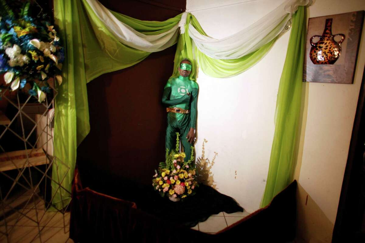 February 2015: The body of Renato Garcia, dressed as fictional superhero the Green Lantern, is propped up against a wall in his sister's apartment, during his wake in San Juan, Puerto Rico, Sunday, Feb. 15, 2015.