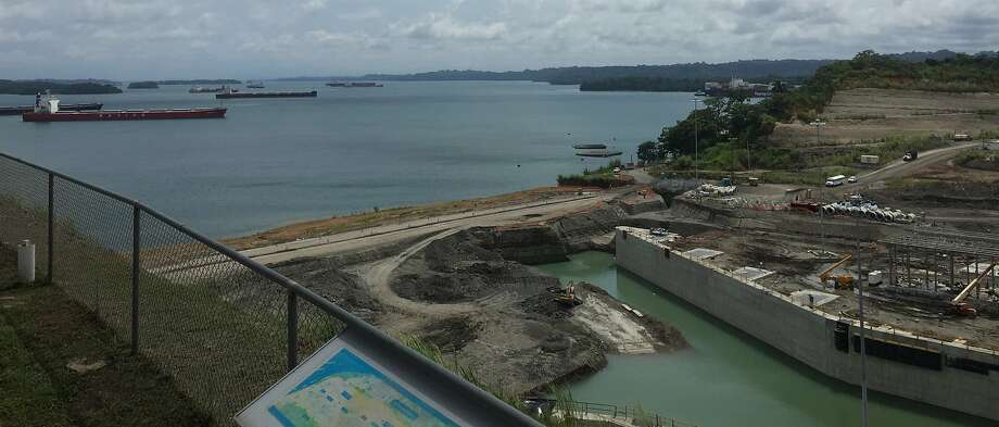 The widened Gatun Locks (foreground) on the Atlantic side of the Panama Canal (seen behind) are still under construction, with completion anticipated next spring. Photo: Lois Kazakoff, San Francisco Chronicle