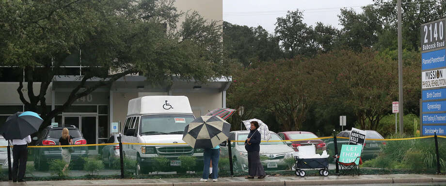 A woman (lower left, facing away) walks Thursday October 22, 2015 toward the entrance of Planned Parenthood at 2140 Babcock road. Abortion protesters with signs and umbrellas were also present. Photo: John Davenport, San Antonio Express-News / ©San Antonio Express-News/John Davenport