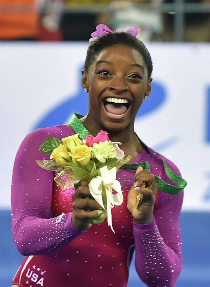 Winner Simone Biles of the US reacts as a bee (top R) buzzes past during the awards ceremony of the women's all-around final at the gymnastics world championships in Nanning on October 10, 2014.   AFP PHOTO/KAZUHIRO NOGIKAZUHIRO NOGI/AFP/Getty Images Photo: KAZUHIRO NOGI, Staff / AFP