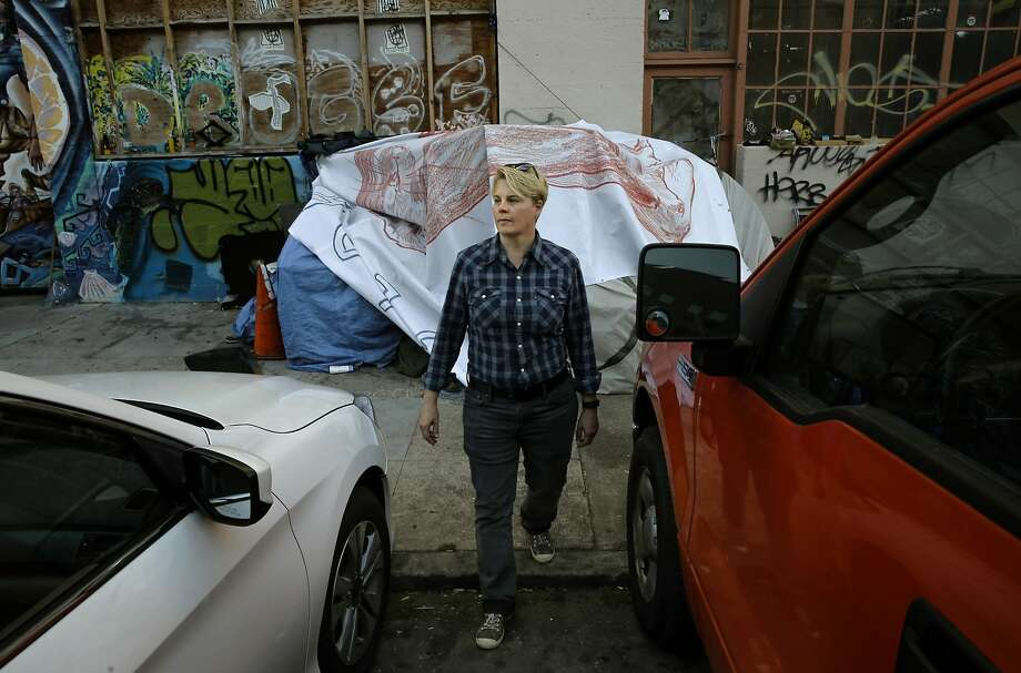 Local merchant Candice Combs stands where a homeless structure has been set up across the street from her business, In Symmetry Wellness Spa, in the Mission Creek neighborhood of San Francisco. Photo: Michael Macor, The Chronicle
