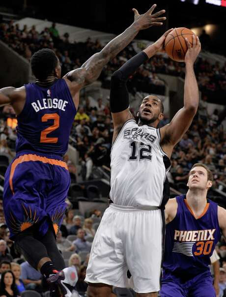 Spurs forward LaMarcus Aldridge shoots against Phoenix Suns guard Eric Bledsoe as Suns forward Jon Leuer (right) looks on during the second half of a preseason NBA basketball game on Oct. 20, 2015, in San Antonio. Photo: Darren Abate /Associated Press / FR115 AP