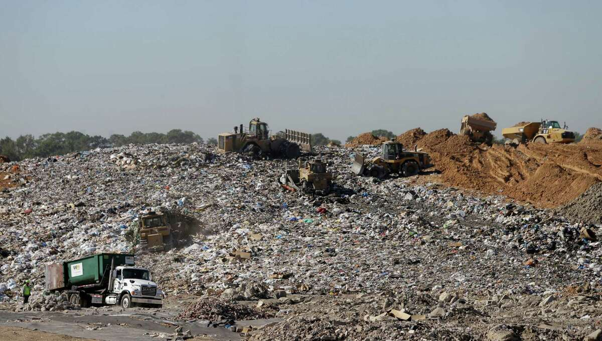 Machines work to compact trash at a landfill as trucks bring dirt that will be used to cover it at the Waste Management Atascocita recycling and disposal facility.