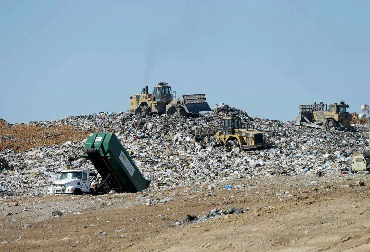 Trash is shown being hauled into the landfill as machines work to compact the trash at the landfill then dirt will be used to cover over the compacted trash at the Waste Management Atascocita Recycling and Disposal Facility, 3623 Wilson Road, is shown Thursday, Oct. 15, 2015, in Humble. ( Melissa Phillip / Houston Chronicle )
