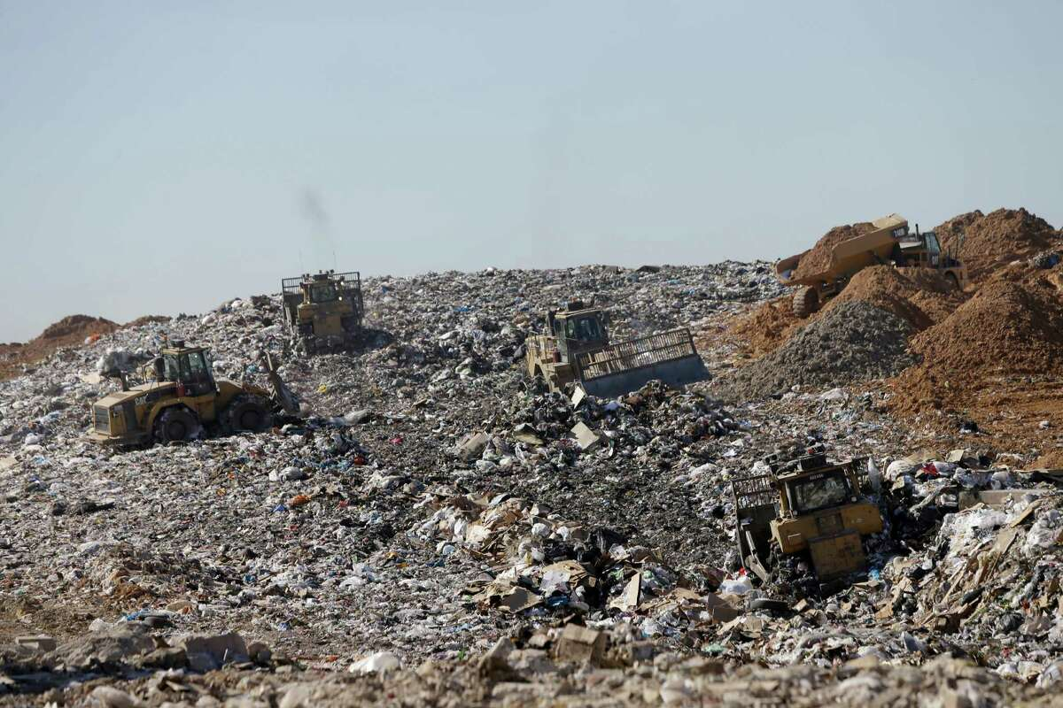 Machines work to compact the trash at the landfill as trucks bring dirt that will be used to cover over the compacted trash at the Waste Management Atascocita Recycling and Disposal Facility, 3623 Wilson Road, is shown Thursday, Oct. 15, 2015, in Humble. ( Melissa Phillip / Houston Chronicle )