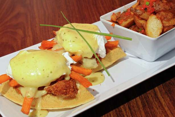 Southern style benny at B-Rad's Bistro Friday, Oct. 16, 2015 in Troy, N.Y. This benny includes poached eggs, crispy fried chicken, sweet potato sticks on waffles topped with hollandaise sauce. This dish is served with home fries. (Lori Van Buren / Times Union)