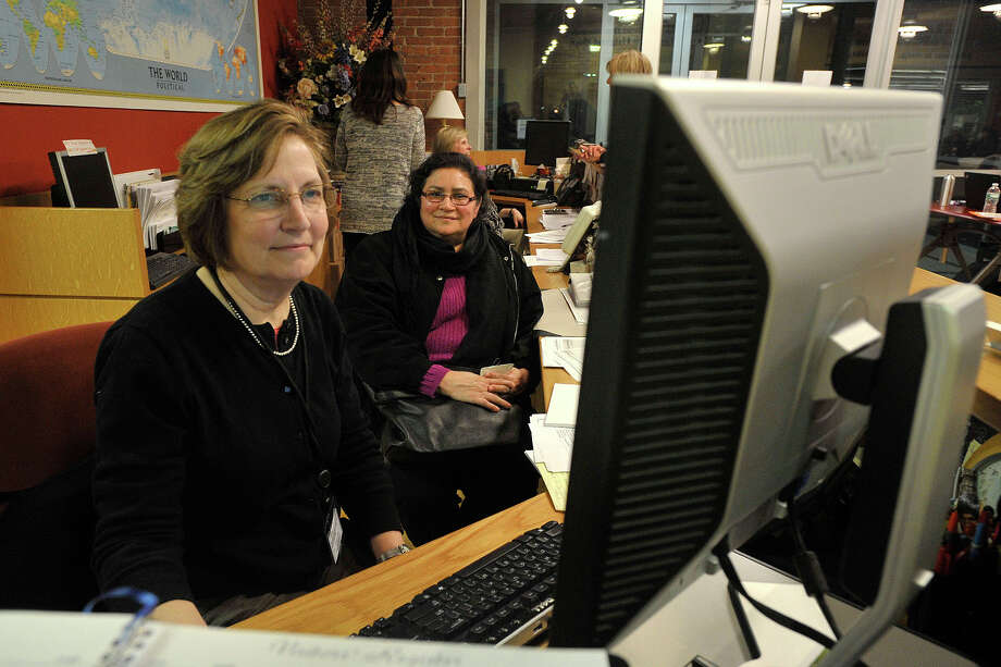 Lorraine Larkin, left, helped Piedad España sign up for Access Health CT at an AmeriCares clinic in Stamford, Conn., during the 2014 open enrollment period. Anthem BlueCross BlueShield remains the market leader with some 1.1 million members in Connecticut. Photo: Jason Rearick / Jason Rearick / Stamford Advocate