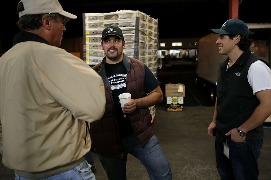 Dimitri Vardakastanis (center) and Bobby Vardakastanis (right) chat with Gary Camarda at the San Francisco Wholesale Produce Market. Photo: Connor Radnovich, The Chronicle