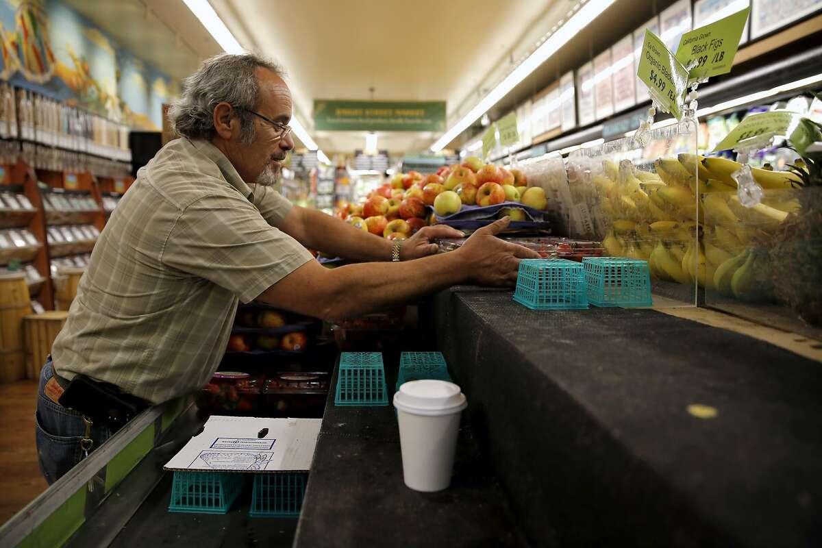 Gus Vardakastanis puts strawberries on display at Haight Street Market in San Francisco, California, on Thursday, Oct. 22, 2015.