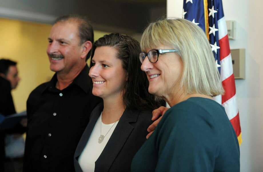 New Stamford police Officer Lindsey Yanicky poses for a photograph with her parents, Glenn and Lynn Yanicky, after being sworn in at the Stamford Government Center. Photo: Autumn Driscoll / Hearst Connecticut Media / Connecticut Post
