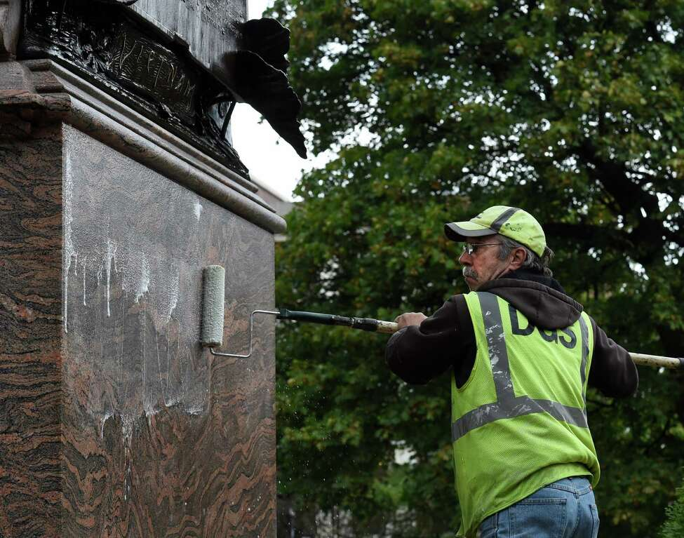 DGS worker Doug Abaire applies sodium hydroxide in an effort to remove graffiti from the face of the Vietnam War Memorial in Academy Park Thursday morning Oct. 22, 2015 in Albany, N.Y. (Skip Dickstein/Times Union)