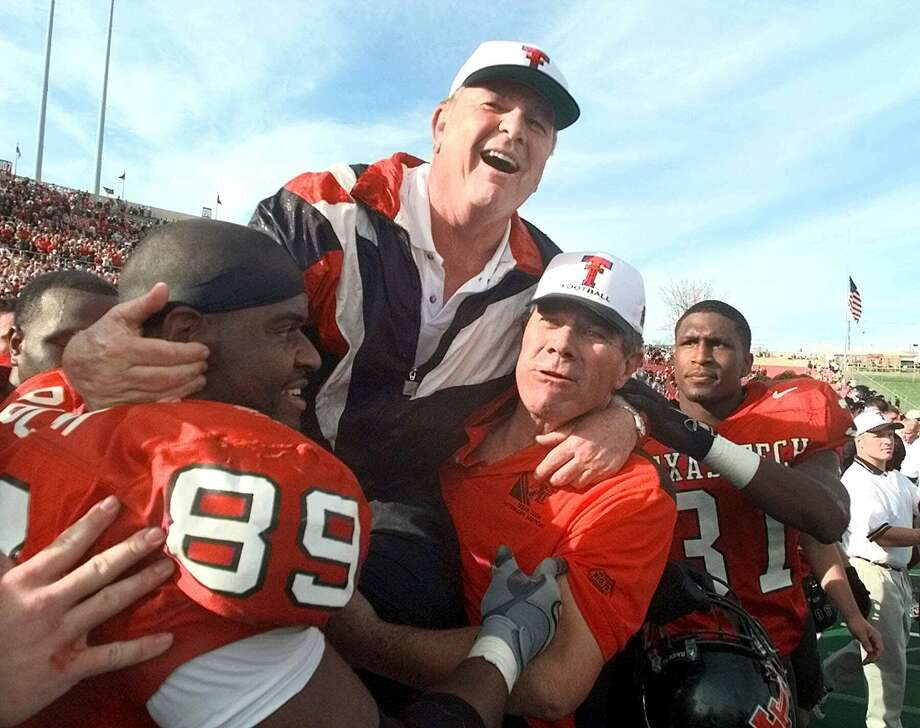 Texas Tech head coach Spike Dykes is lifted by Texas Tech alum and All-American E.J. Holub, right, and Taurus Rucker (89) after beating Oklahoma 38-28 in Lubbock on Nov. 20, 1999. Dykes announced his retirement after the game. Photo: Lm Otero /Associated Press / AP