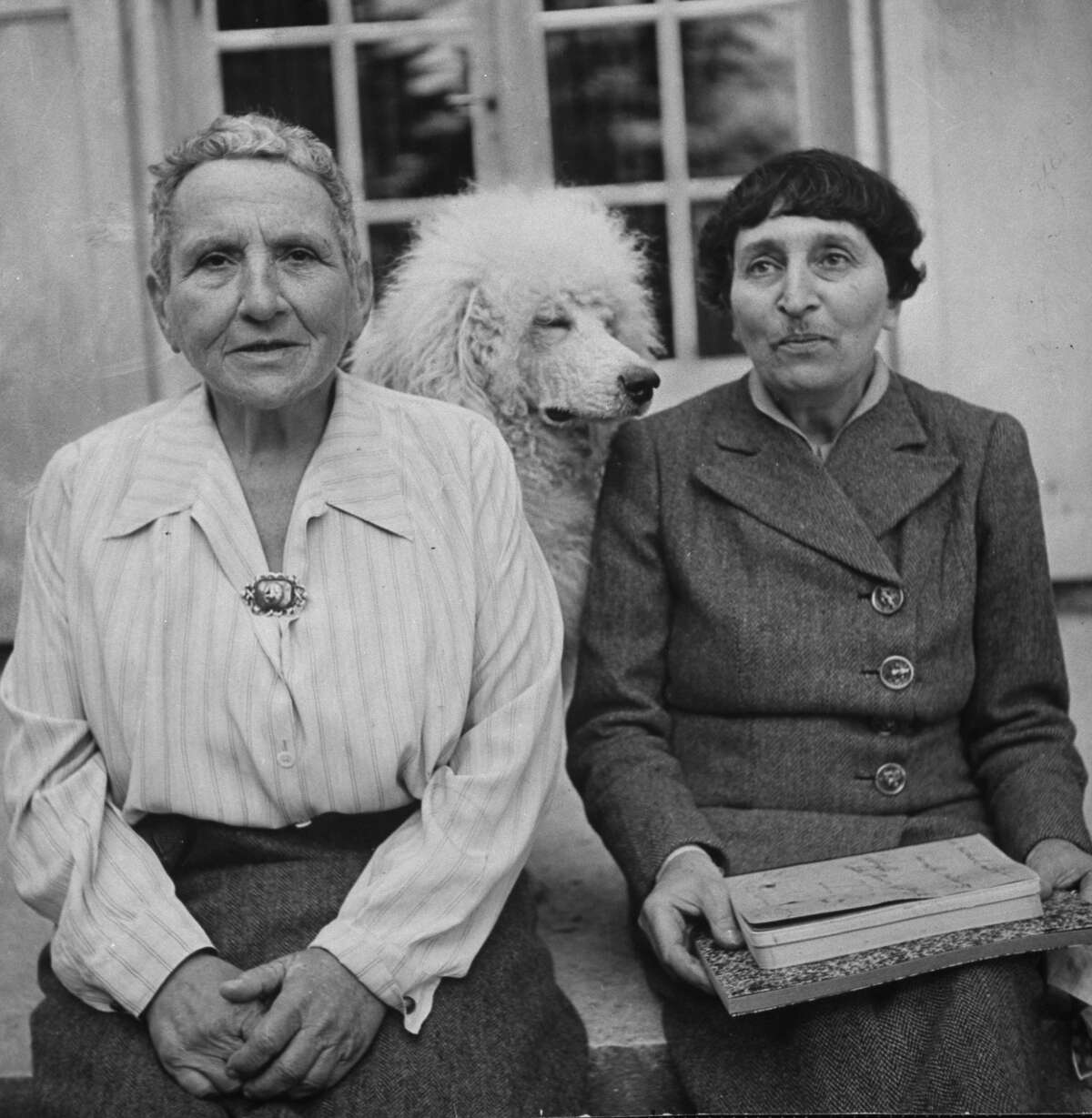 Author Gertrude Stein, left, 70, America's most famous expatriate, posing with her companion Alice B. Toklas and their white poodle on the doorstep of her house. Some say the ghost of Toklas is haunting the Sorrento Hotel. Photo taken Sept. 1, 1944.