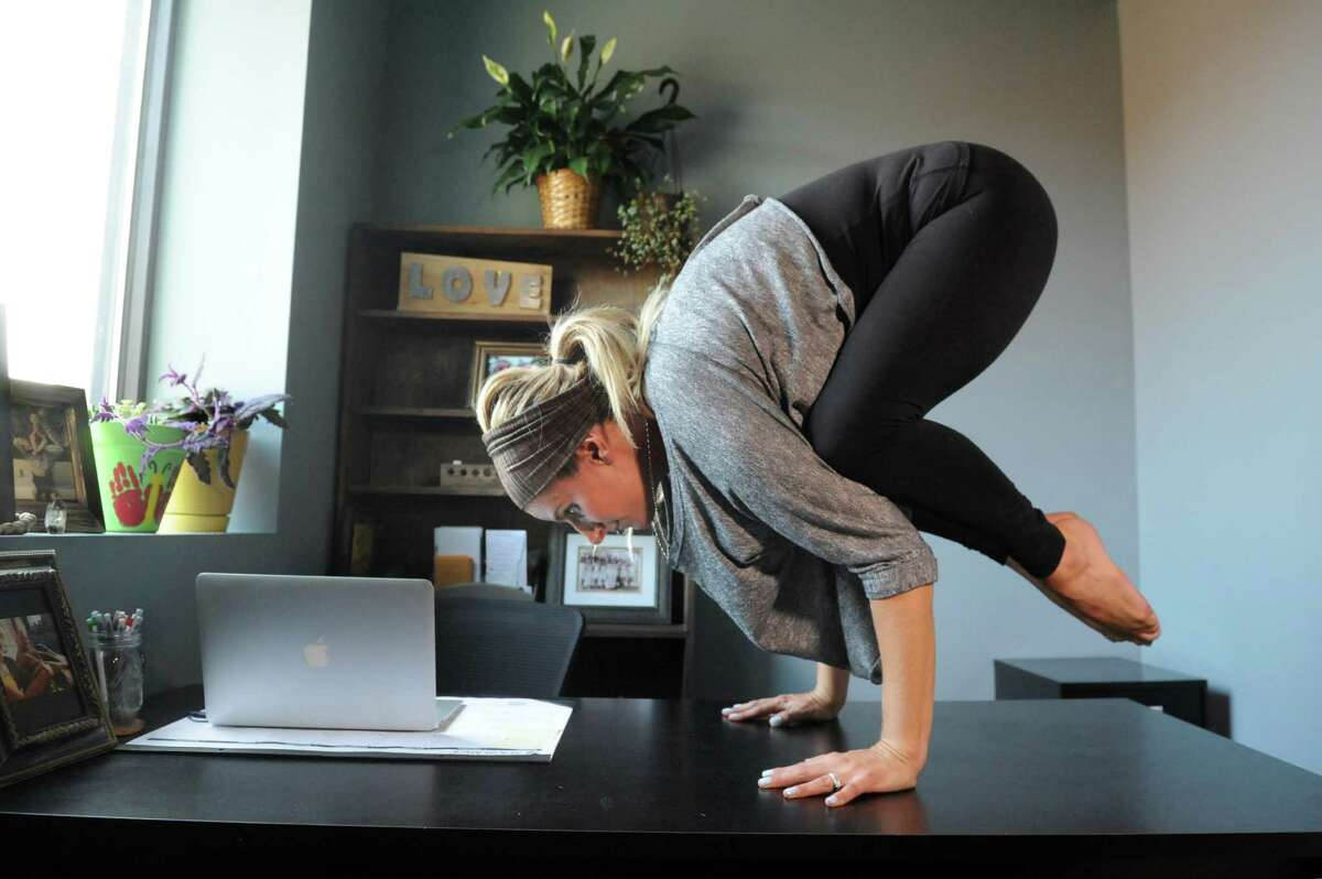 Meg Allen holds a crow pose on top of her desk on Wednesday, Sept. 2, 2015, at JAI yoga studio in Albany, N.Y. (Cindy Schultz / Times Union)