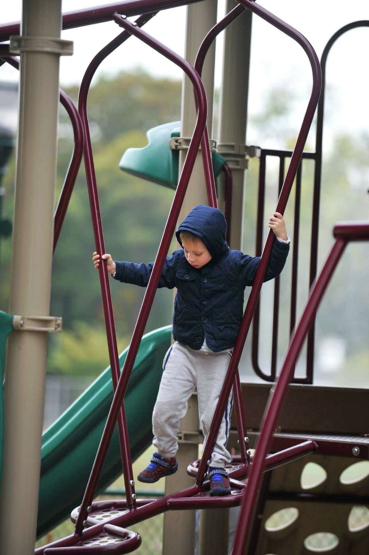 Three year old Lucca Martini, of Stamford, carefully crosses an obstacle on the Scalzi Park playground on Thursday, Oct. 22, 2015.