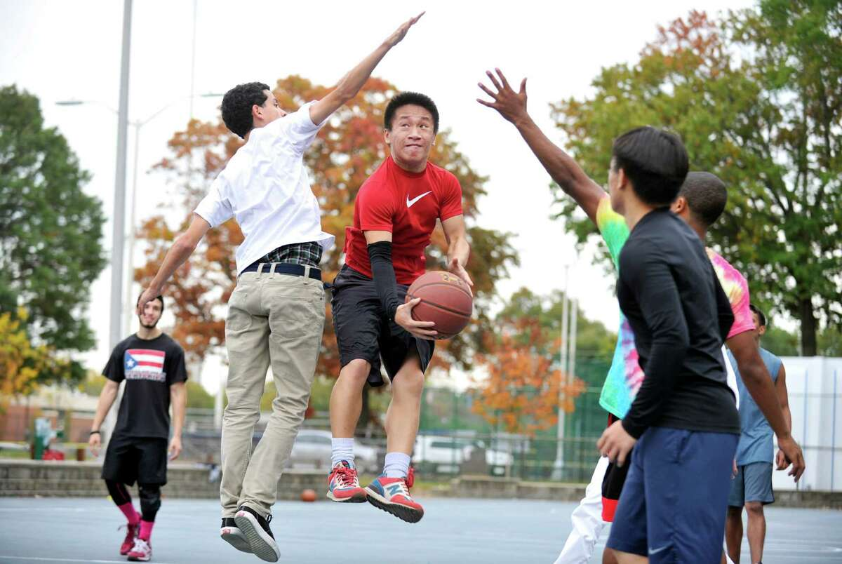 UConn Stamford student Thomas Phung, 18, weaves through his friends for a shot during a pickup basketball game on Thursday, Oct. 22, 2015.