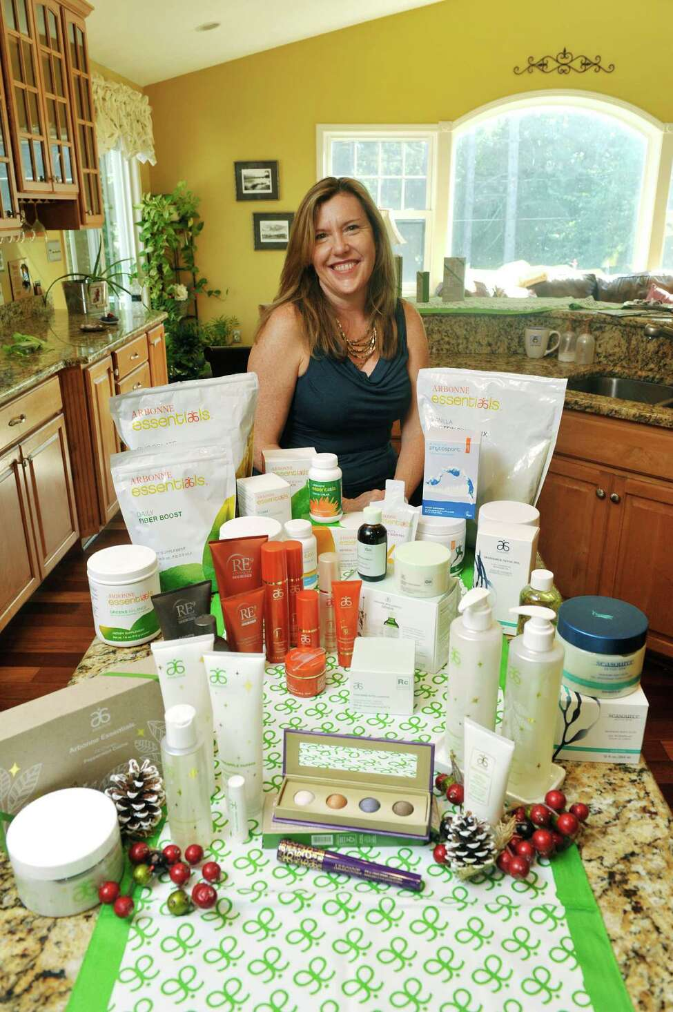 Theresa Marangas, an Arbonne independent consultant, poses for a photograph for some of the Arbonne products at her home. (Paul Buckowski / Times Union)