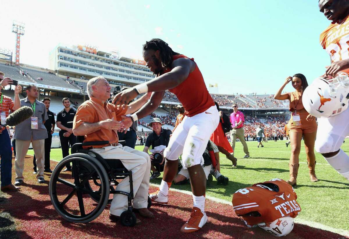 Texas governor Greg Abbott greets Malik Jefferson #46 of the Texas Longhorns after a 24-17 win against the Oklahoma Sooners during the 2015 AT&T Red River Showdown at Cotton Bowl on October 10, 2015 in Dallas, Texas. (Photo by Ronald Martinez/Getty Images)