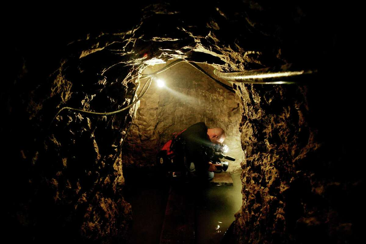 OTAY MESA, CA - JANUARY 30: Cameraman Mike Gold films through a drug tunnel found along the Mexico/USA Border at a warehouse January 30, 2006 in Otay Mesa, California. The tunnel runs 2,400 feet; is furnished with lighting, ventilation and equipment to pump out ground water and was used to funnel drugs into the United States from Mexico.