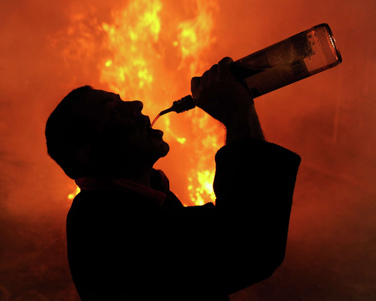 A man drinks liquor from a bottle besides a bonfire on January 16, 2012 in the small village of San Bartolome de Pinares, Spain.