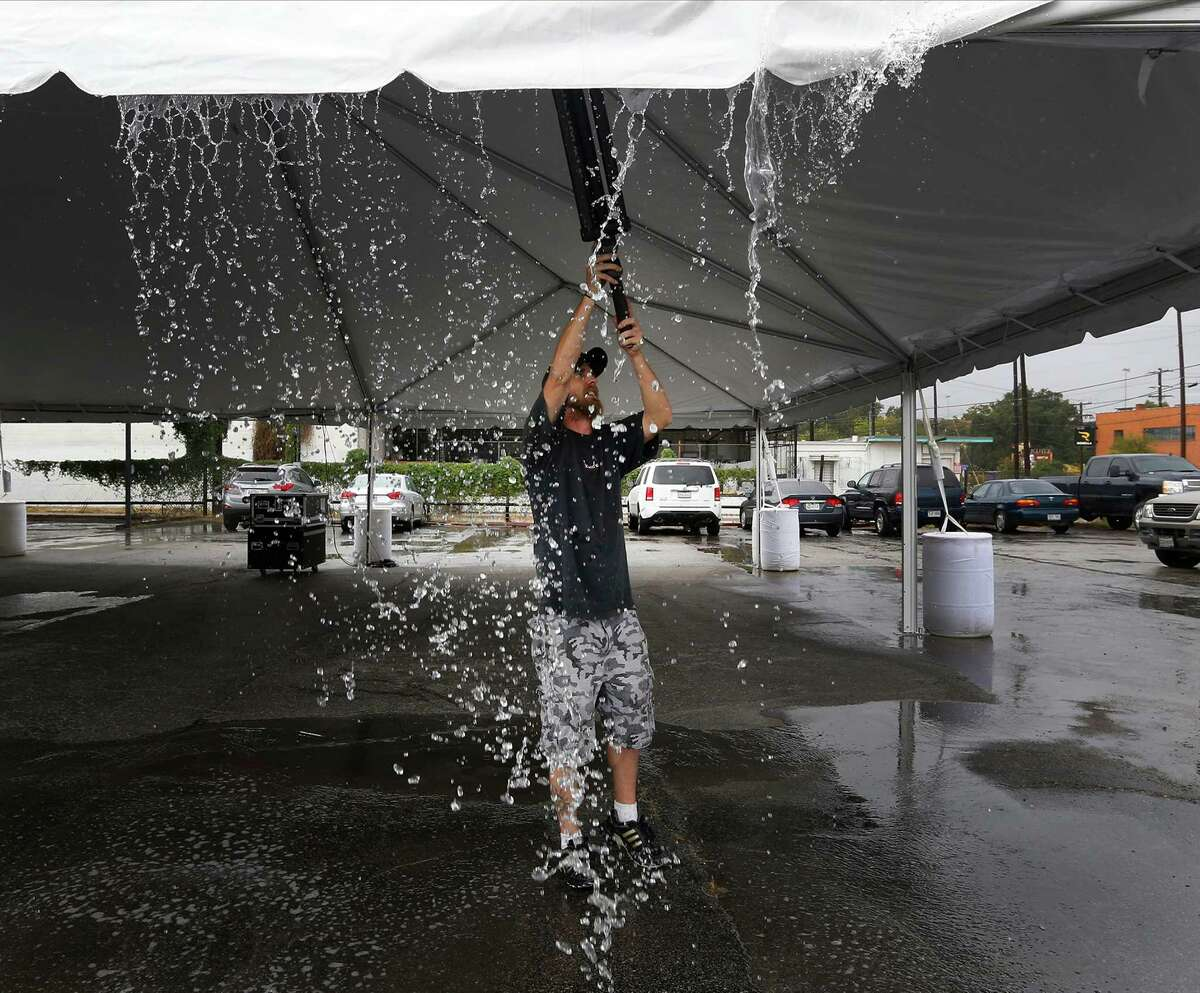 Josh Stoker clears off collected rain water on a tent where he was helping set up stage lighting and sound in preparation for the upcoming Luminaria arts festival along the stretch of the River North neighborhood on Thursday, Oct. 22, 2015. Luminaria, which started in 2008, features a variety of artwork from local, national and international artists. The event will be taking place this weekend - rain or shine.