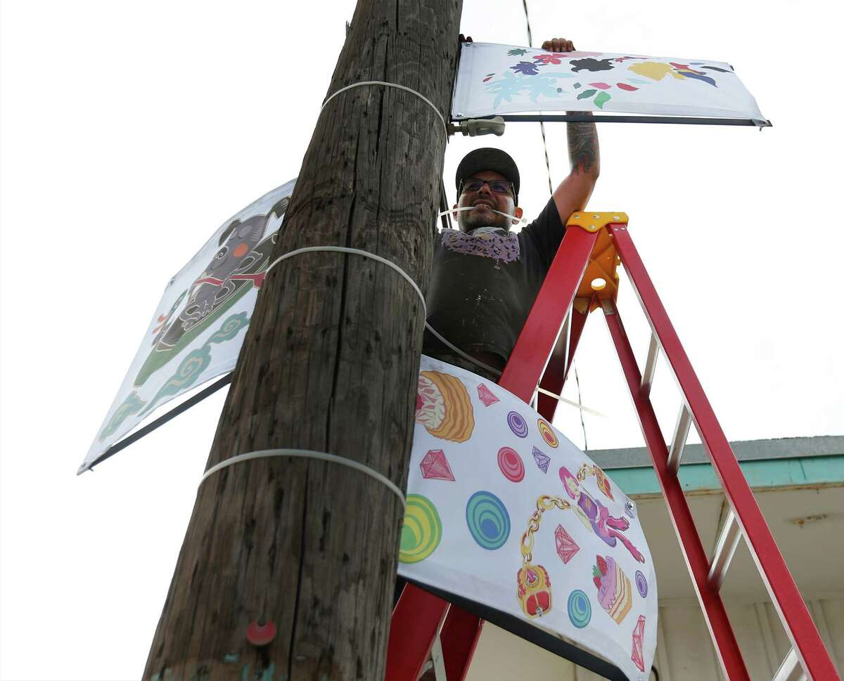 Art installer Pedro Luera hangs up reproductions of artwork from local artists as part of the City of San Antonio Department of Culture and Creative Development's public art project called RESYMBOL along Jones Avenue on Thursday, Oct. 22, 2015. The public artwork is shown in conjunction with the upcoming Luminaria arts festival along the stretch of the River North neighborhood which will be taking place this weekend - rain or shine. The reproductions being hung up by Luera are from artists: Robert Tatum (from clockwise left), Waddy Armstrong and Elizabeth Carrington.