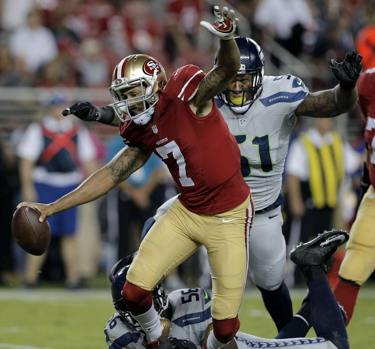 Colin Kaepernick (7) is sacked by Cliff Avril (56) with help from Bruce Irvin (51) in the first half of the 49ers game against the Seattle Seahawks at Levi's Stadium in Santa Clara, Calif., on Thursday, October 22, 2015.