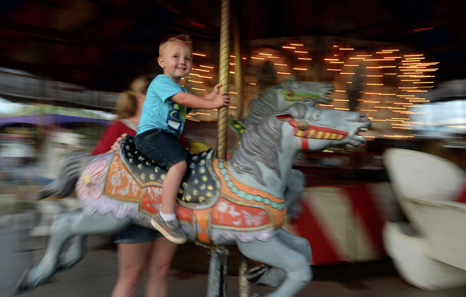 Tyler Leyendecker, 2, and mom Jessica Leyendecker take a spin on the merry-go-round on the opening night of the Village Creek Festival in Lumberton City Park Thursday. The festival continues from 2 p.m.-midnight Friday and 10 a.m.-11 p.m. Saturday at Lumberton City Park, 1300 FM 421, Lumberton. The event is the major fundraiser for the Lumberton Chamber of Commerce and features carnival rides, food and arts and crafts booths. Highlights include a costume contest Friday and the Miss Village Creek Pageant on Saturday. Admission is free, parking $5. (409) 744-0554.  Photo taken Thursday, October 22, 2015  Kim Brent/The Enterprise Photo: Kim Brent / Beaumont Enterprise