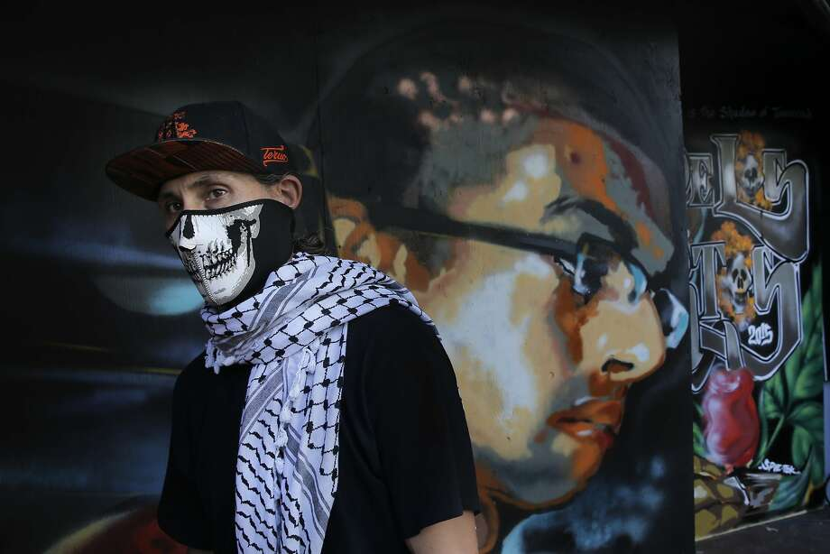 Local muralist Eric Norberg, wearing his Day of the Dead mask on Thurs. October 22, 2015, in San Francisco, Calif., in front of the mural he has  created in honor of Antonio Ramos who was shot and killed in Oakland as Ramos painted a mural. Norberg was a mentor to Antonio Ramos, the mural is at the entrance to SOMArt's Day of the Dead exhibit. Photo: Michael Macor, The Chronicle