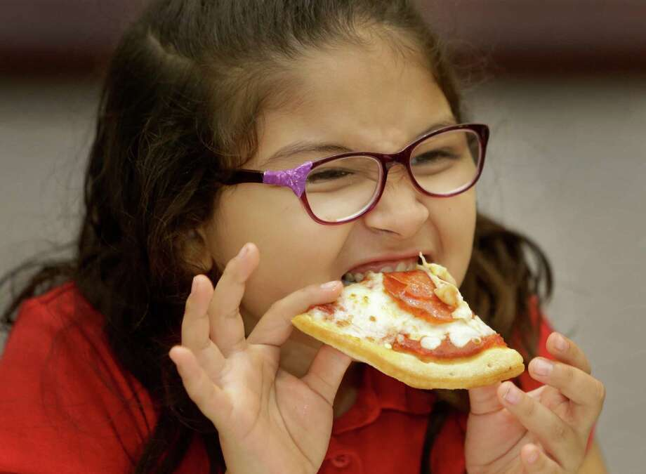 Melanie Cerda, 8, a third grader at North Shore Elementary in Galena Park ISD, samples pizza during the Harris County Department of Education's 2015 School Nutrition Expo at Humble Civic Center, 8233 Will Clayton Parkway,  Thursday, Oct. 22, 2015, in Humble. Approximately 150 students taste-tested cafeteria food from 60 vendors alongside their school district nutrition directors and completed a survey. Choice Partners gathers that information to decide on future food contracts with vendors who are awarded contracts for groceries, dairy products, bread, produce and other food products. Photo: Melissa Phillip, Houston Chronicle / © 2015 Houston Chronicle