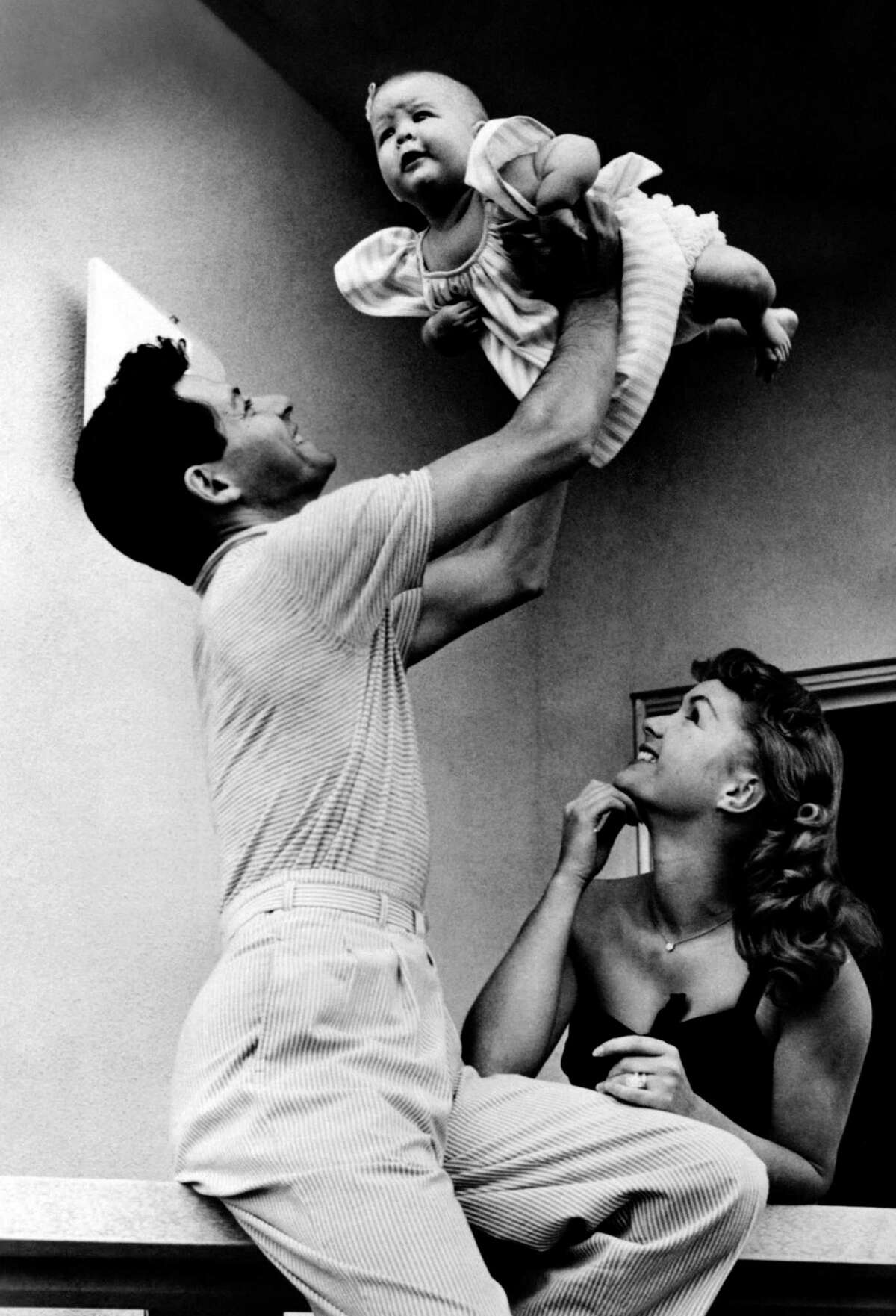 Carrie Fisher (that's her being held aloft) was born Oct. 21, 1956, the daughter of singer Eddie Fisher (left) and actress Debbie Reynolds (right). This photo was taken in 1957, but the source doesn't say when.
