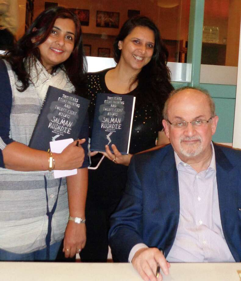 """Tina Munshani, left, of Easton and Ritu Johorey of Westport pose Thursday with writer Salman Rushdie at Staples High School. Rushdie delivered the Westport Library's 13th annual Malloy Lecture in the Arts before an audience of about 950 people. He read from his latest novel, """"Two Years Eight Months and Twenty-Eight Nights,"""" and took questions from the audience. Photo: Meg Barone / For Hearst Connecticut Media / Westport News"""