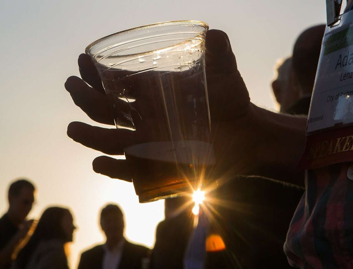 Adam Lenz, a member of the Annual Meeting of The Minds, an event where the future of urban sustainability is reviewed, mingles outside Craneway Pavilion on Ford Point drinking beer made from recycled grey water on Thursday, Oct. 22, 2015 in Richmond, Calif.