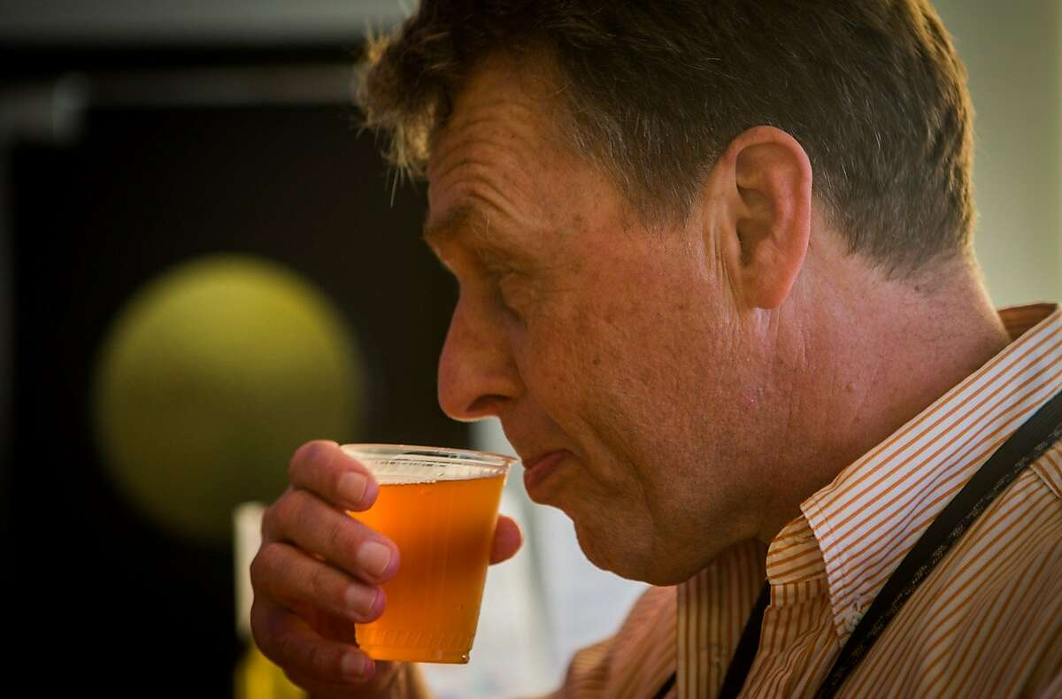 Ken Homer takes his first sip of a recycled grey water beer being sampled at the Annual Meeting of The Minds, an event where the future of urban sustainability is reviewed, in Craneway Pavilion on Ford Point on Thursday, Oct. 22, 2015 in Richmond, Calif.