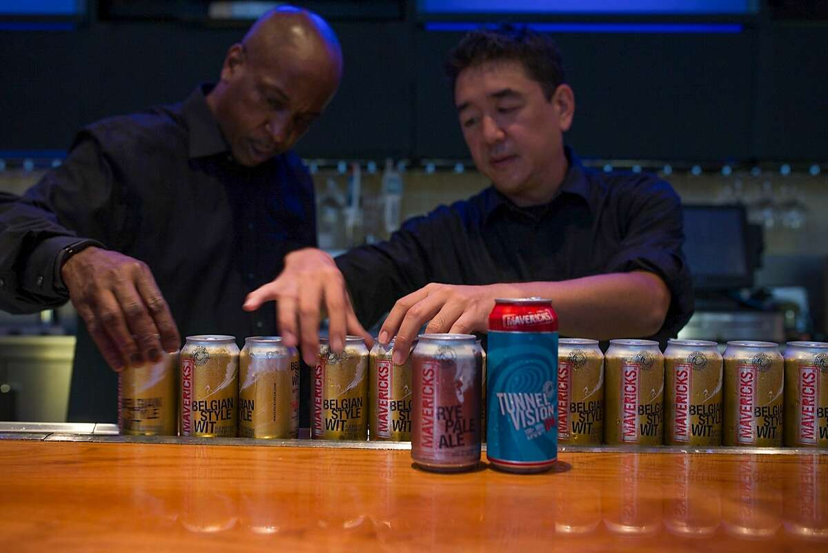 From left, Wendell Smith and Brandon Cono, bartenders at the Annual Meeting of The Minds, an event where the future of urban sustainability is reviewed, add beer cans to the display on the bar in Craneway Pavilion on Thursday, Oct. 22, 2015 in Richmond, Calif.