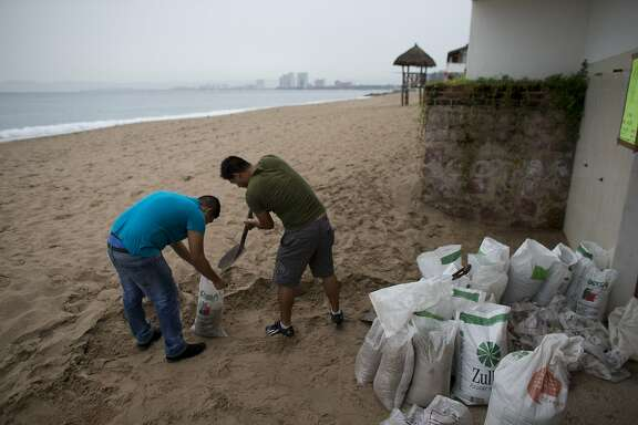 """Men fill small bags with sand from the beach as they prepare for the arrival of Hurricane Patricia in Puerto Vallarta, Mexico, Friday, Oct. 23, 2015. Patricia headed toward southwestern Mexico Friday as a monster Category 5 storm, the strongest ever in the Western Hemisphere that forecasters said could make a """"potentially catastrophic landfall"""" later in the day. (AP Photo/Rebecca Blackwell)"""