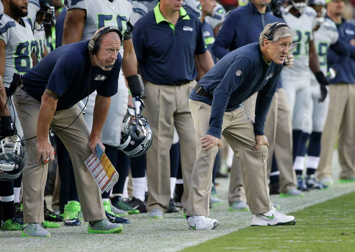 Seattle Seahawks assistant coach Tom Cable, left, and Pete Carroll watch during the first half of an NFL football game against the San Francisco 49ers in Santa Clara, Calif., Thursday, Oct. 22, 2015. (AP Photo/Marcio Jose Sanchez)