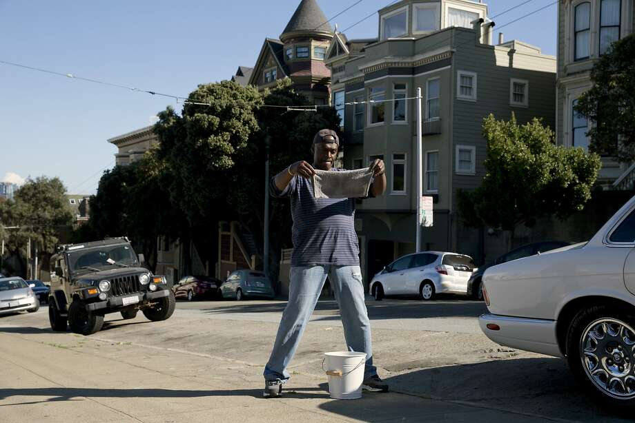 William King wrings out a rag he uses to wash his 1998 Jaguar XJ8 at Alamo Square Park. Photo: Erin Brethauer, The Chronicle