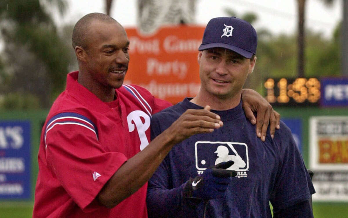 Philadelphia Phillies outfielder Brian L. Hunter, left, greets Detroit Tigers catcher Scott Servais as they walk across the rain-soaked outfield at Jack Russell Stadium, Sunday, March 4, 2001, in Clearwater Fla., shortly before their exhibition baseball game was called because of rain.
